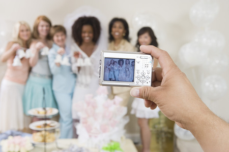 Person photographing women at bridal shower