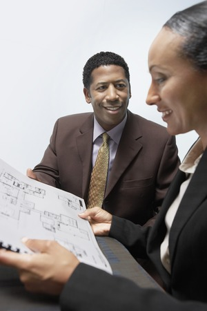decisionmaking: Businessman and Businesswoman in Meeting LANG_EVOIMAGES