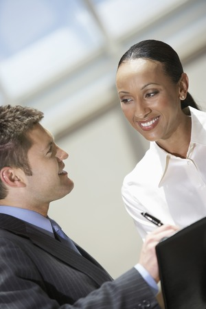 racially diverse: Businessman and Businesswoman in Meeting LANG_EVOIMAGES