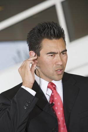 hands free: Hombre de negocios mediante tel�fono m�vil con manos libres, en el interior