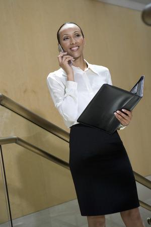 階段の上に携帯電話を使用してビジネスの女性 写真素材