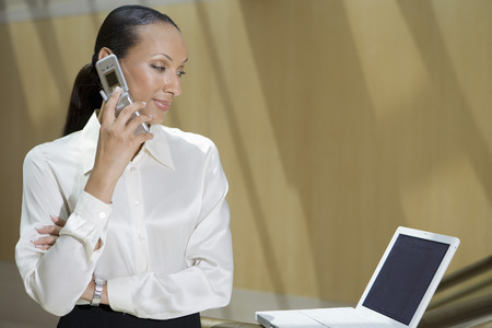 オフィスで携帯電話とラップトップを使用してビジネスの女性