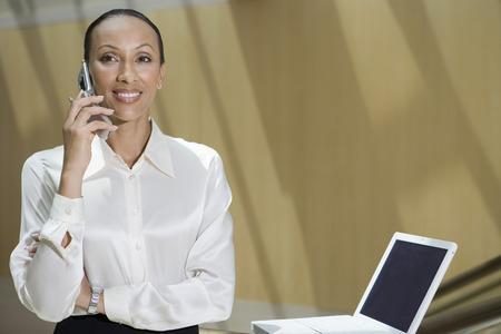 ビジネスの女性のオフィスで携帯電話を使用して