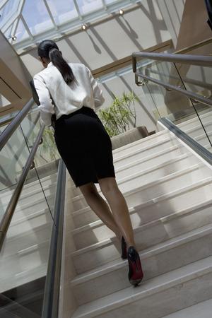 ビジネスの女性の事務所ビルの 2 階に行く