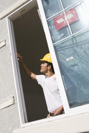 Construction Worker examining window frame Stock Photo - 5412219