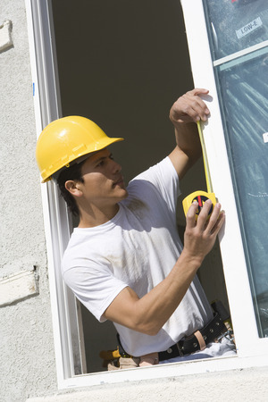 Construction Worker measuring window frame Stock Photo - 5412228