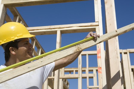 Construction worker measuring plank Stock Photo - 5412264