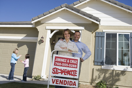 Portrait of mid-adult couple in front of new house, children (6-9) in background Stock Photo - 5475490