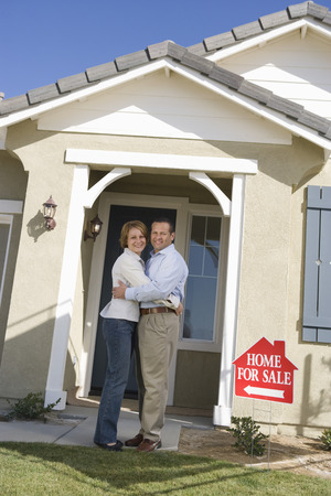 Mid-adult couple in front of new house, portrait Stock Photo - 5475493