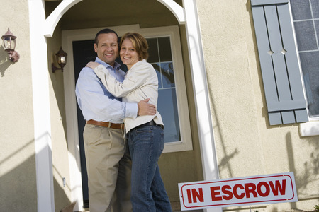 Mid-adult couple in front of new house, portrait Stock Photo - 5475494