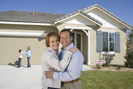 Portrait of mid-adult couple in front of new house, children (6-9) in background Stock Photo - 5475495