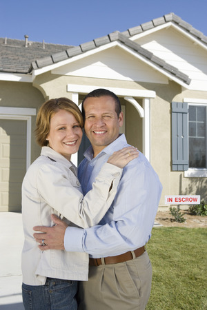 Mid-adult couple in front of new house, portrait Stock Photo - 5475496