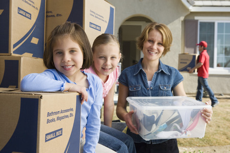 Portrait of mother with two daughters (6-9) by cardboard boxes Stock Photo - 5475522