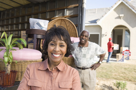 middle easterners: Middle-aged couple in front of lorry with furniture