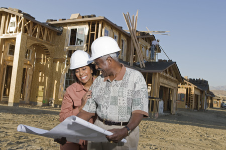Middle-aged couple watching blueprints at construction site Stock Photo - 5475538