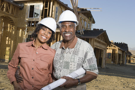Middle-aged couple holding blueprints at construction site, portrait Stock Photo - 5475539