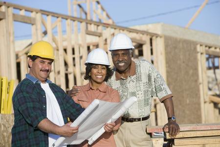 建設現場で青写真と一緒に 2 つの男女の肖像画 写真素材