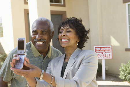 Middle-aged couple photographing in front of new home Stock Photo - 5475546
