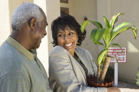 中年のカップルの新しい家、鉢植えに女性の前に
