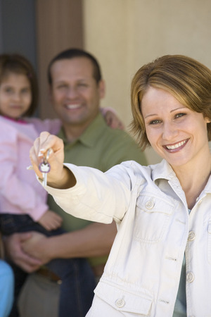 middle easterners: Mid-adult woman with key to new home, others in background LANG_EVOIMAGES