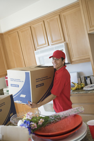 middle easterners: Man carrying a box in kitchen