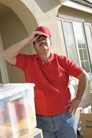 middle easterners: Mid-adult man putting on baseball cap, outdoors LANG_EVOIMAGES