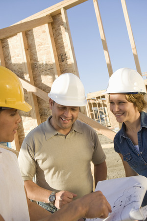 middle easterners: Two men and woman with blueprints at construction site, portrait