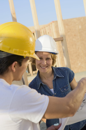 middle easterners: Man and woman looking at blueprints, construction site