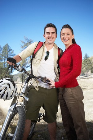 Smiling Young Couple Mountain Biking Stock Photo - 5475567