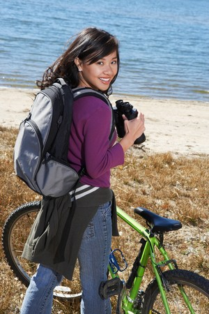 twentysomething: Young Woman on Mountain Bike Using Binoculars LANG_EVOIMAGES