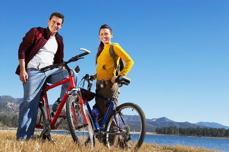 mountain bicycling: Young Couple on Mountain Bikes LANG_EVOIMAGES