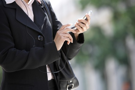 Businesswoman Dialing Cell Phone Stock Photo - 5475578
