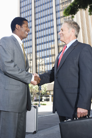 Two businessmen shaking hands, outdoors Stock Photo - 5412200