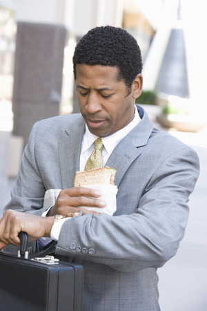 Businessman eating sandwich and checking time Stock Photo - 5412201