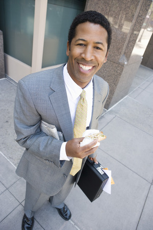 Portrait of businessman with newspaper and sandwich, smiling Stock Photo - 5475585