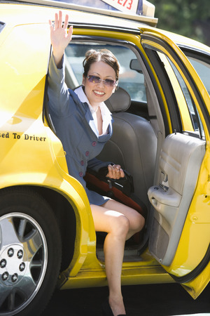 Young businesswoman disembarking from taxi Stock Photo - 5475592