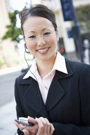 Portrait of young businesswoman with mobile and bluetooth Stock Photo - 5475602