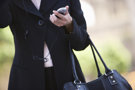 Businesswoman with handbag and  mobile, mid section Stock Photo - 5475603