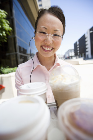 coffees: Portrait of young woman with take-away coffees, outdoors