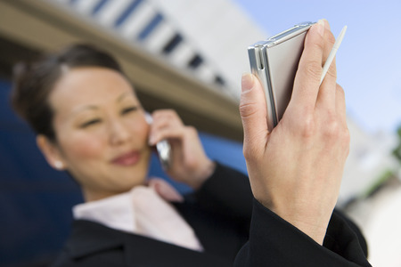Young businesswoman using mobile and PDA Stock Photo - 5475619
