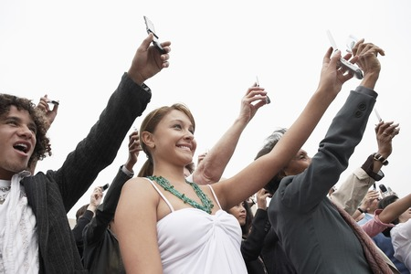 multiple ethnicity: People Raising Cell Phones at Rally