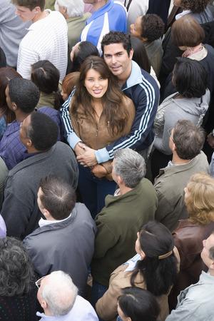 mixed age range: Pareja joven abrazando entre la multitud