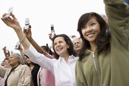 mixed age range: Crowd holding up mobile phones