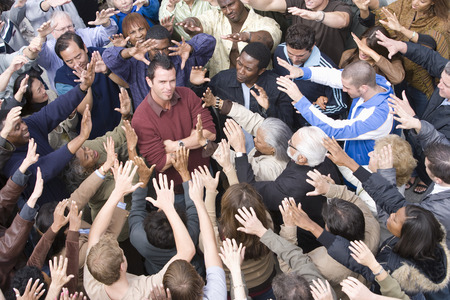 mixed age range: Young man surrounded by crowd