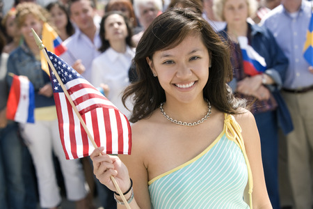 1 and crowd: Young woman holding American flag, portrait