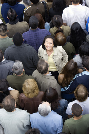 mixed age range: Woman standing among crowd LANG_EVOIMAGES