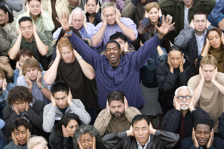 Man celebrating among crowd covering ears Stock Photo - 5475693