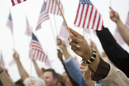mixed age range: Crowd holding up American flags