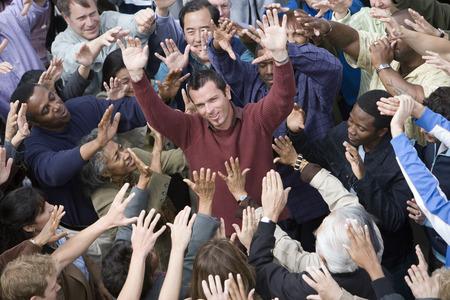 Crowd with arms raised surrounding man Stock Photo - 5475699