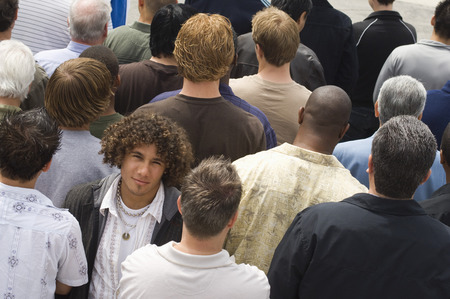 conformity: Young man standing in crowd
